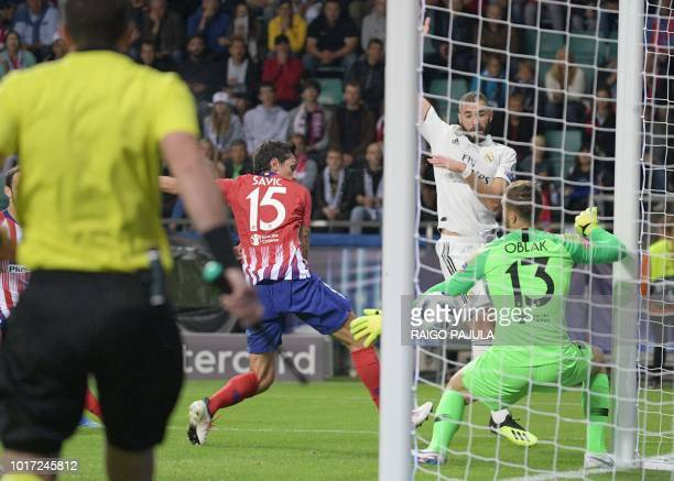 Atletico Madrid's Slovenian goalkeeper Jan Oblak fails to save a ball shot by Real Madrid's French forward Karim Benzema as Atletico Madrid's...