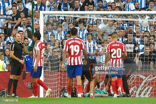Atletico Madrid's Slovenian goalkeeper Jan Oblak is treated by medical staff during the Spanish league football match Real Sociedad against Club...