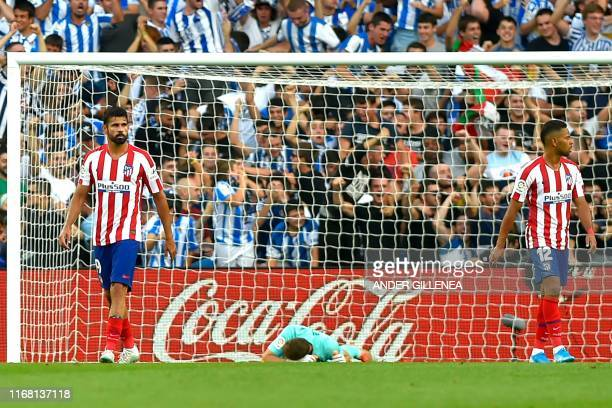 Atletico Madrid's Slovenian goalkeeper Jan Oblak lies on the ground after Real Sociedad's Spanish defender Nacho Monreal scored a goal during the...