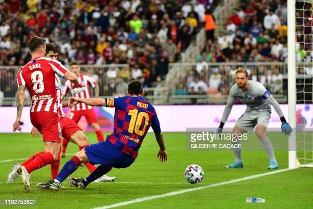 Atletico Madrid's Slovenian goalkeeper Jan Oblak watches as Atletico Madrid's Spanish midfielder Saul Niguez marks Barcelona's Argentine forward...
