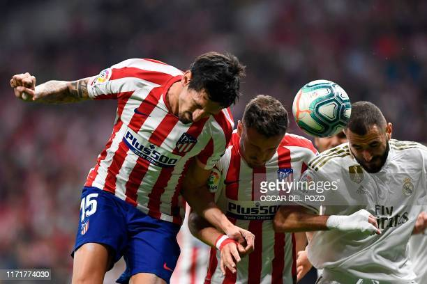 Atletico Madrid's Spanish defender Mario Hermoso Atletico Madrid's Spanish midfielder Saul Niguez and Real Madrid's French forward Karim Benzema head...