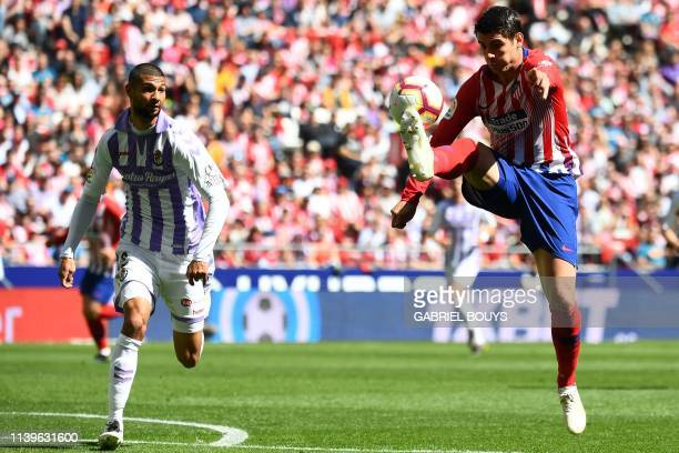 Atletico Madrid's Spanish forward Alvaro Morata challenges Real Valladolid's Spanish defender Joaquin during the Spanish League football match...