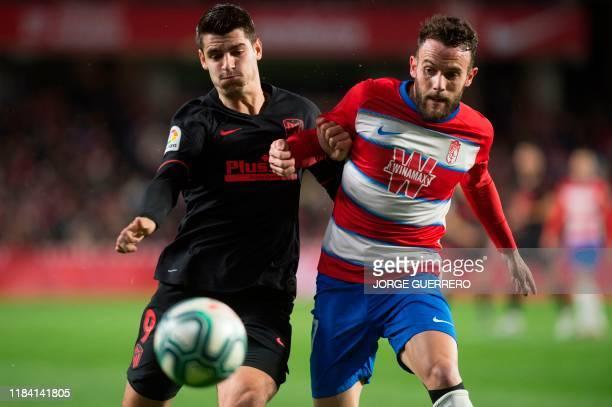 Atletico Madrid's Spanish forward Alvaro Morata vies with Granada's Spanish defender Quini Marin during the Spanish league football match Granada FC...