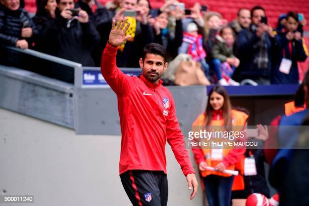Atletico Madrid's Spanish forward Diego Costa acknowledges supporters at the start of a training session following his welcoming ceremony at the...