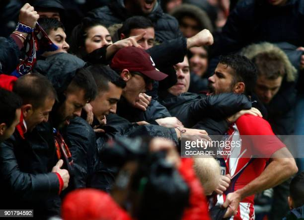 TOPSHOT Atletico Madrid's Spanish forward Diego Costa celebrates a goal with supporters during the Spanish league football match Club Atletico de...