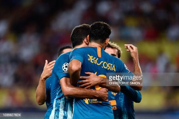 Atletico Madrid's Spanish forward Diego Costa celebrates with teammates after scoring a goal during the UEFA Champions League first round football...