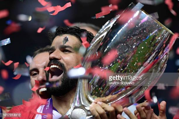 Atletico Madrid's Spanish forward Diego Costa celebrates with the trophy at the end of the UEFA Super Cup football match between Real Madrid and...