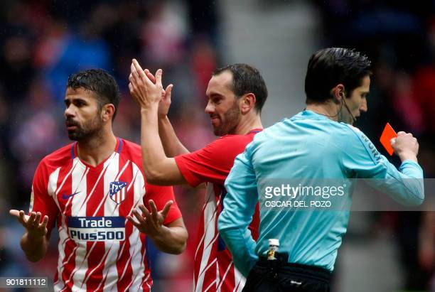 Atletico Madrid's Spanish forward Diego Costa gestures beside Atletico Madrid's Uruguayan defender Diego Godin after being shown a red card for...