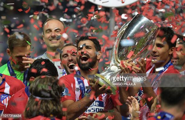 Atletico Madrid's Spanish forward Diego Costa holds the trophy as he celebrates with teammates after winning the UEFA Super Cup football match...