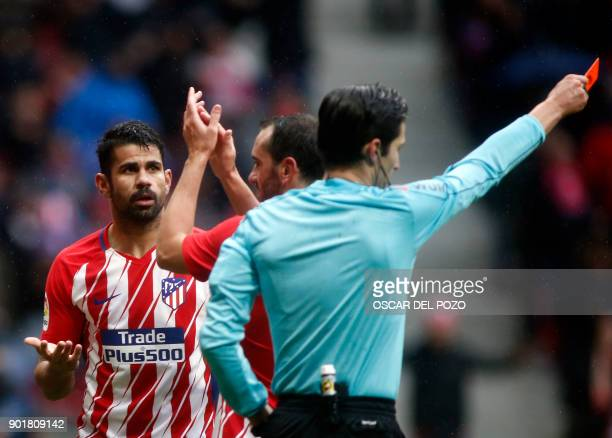 Atletico Madrid's Spanish forward Diego Costa is shown a red card after celebrating a goal with supporters during the Spanish league football match...