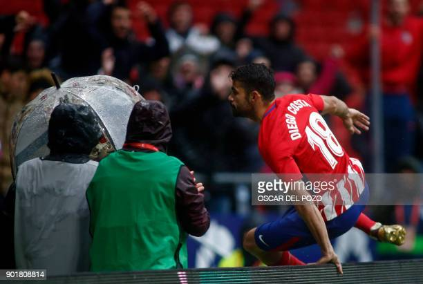 Atletico Madrid's Spanish forward Diego Costa jumps a barrier to celebrate a goal with supporters during the Spanish league football match Club...