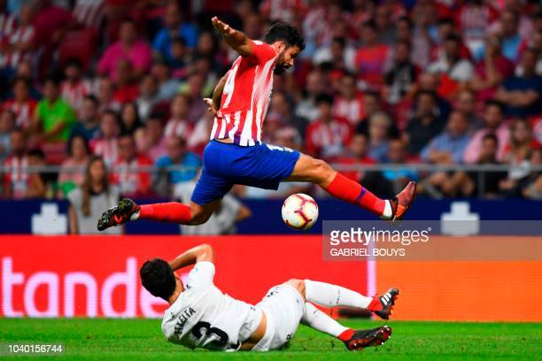 Atletico Madrid's Spanish forward Diego Costa jumps over SD Huesca's Spanish defender Xabier Etxeita during the Spanish league football match Club...