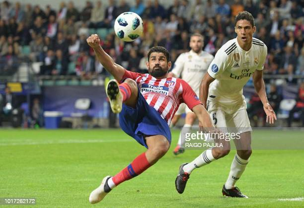 Atletico Madrid's Spanish forward Diego Costa kicks the ball as Real Madrid's French defender Raphael Varane looks on during the UEFA Super Cup...