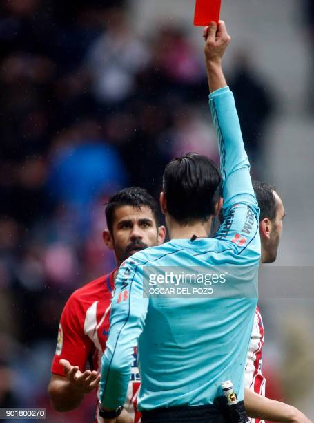 Atletico Madrid's Spanish forward Diego Costa receives a red card after celebrating a goal with supporters during the Spanish league football match...