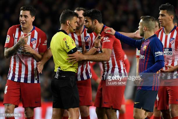 Atletico Madrid's Spanish forward Diego Costa talks with Spanish referee Gil Manzano prior to receiving a red card during the Spanish league football...