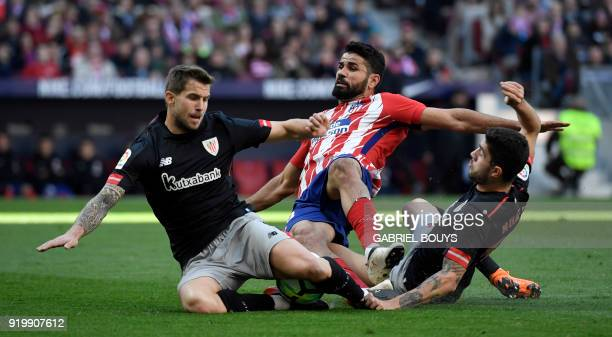 Atletico Madrid's Spanish forward Diego Costa vies with Athletic Bilbao's Spanish defender Inigo Martinez and Athletic Bilbao's Spanish defender Unai...