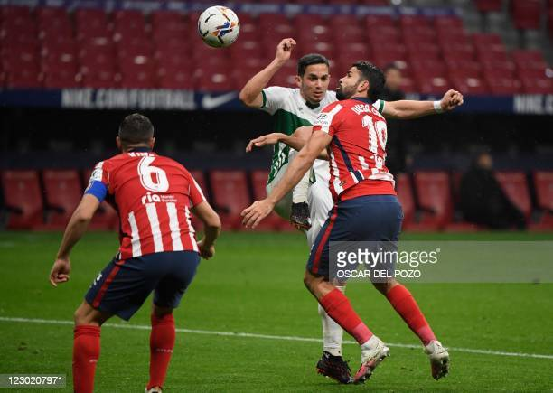 Atletico Madrid's Spanish forward Diego Costa vies with Elche's Argentinian midfielder Ivan Marcone during the Spanish league football match between...