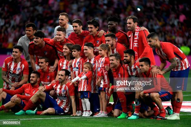 Atletico Madrid's Spanish forward Fernando Torres and his children Nora Leo and Elsa pose with his teammates during a tribute at the end of the...