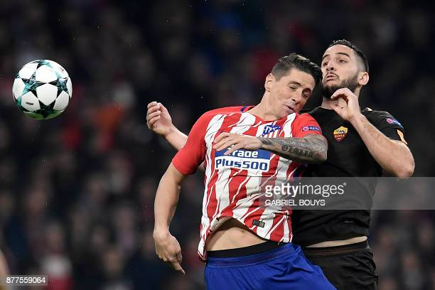 Atletico Madrid's Spanish forward Fernando Torres heads the ball with Roma's Greek defender Kostas Manolas during the UEFA Champions League group C...