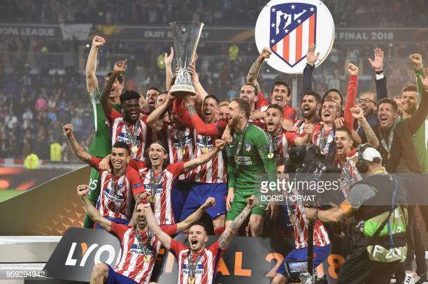 Atletico Madrid's Spanish forward Fernando Torres holds the trophy past teammates after winning the UEFA Europa League final football match between...