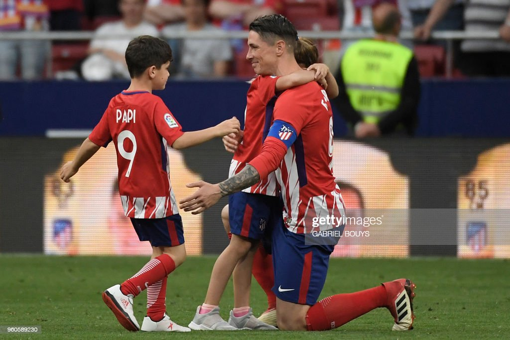 TOPSHOT - Atletico Madrid's Spanish forward Fernando Torres hugs two of his children Nora and Leo during a tribute at the end of the Spanish league football match between Club Atletico de Madrid and SD Eibar at the Wanda Metropolitano stadium in Madrid on May 20, 2018. - Torres scored twice in what was his final match for Atletico Madrid.