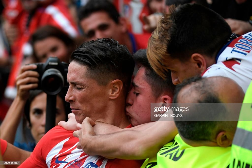 TOPSHOT - Atletico Madrid's Spanish forward Fernando Torres (L) is kissed by fans after scoring a goal during the Spanish league football match between Club Atletico de Madrid and SD Eibar at the Wanda Metropolitano stadium in Madrid on May 20, 2018.