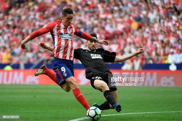 Atletico Madrid's Spanish forward Fernando Torres kicks the ball to score past Eibar's Portuguese defender Paulo Rodrigues during the Spanish league...