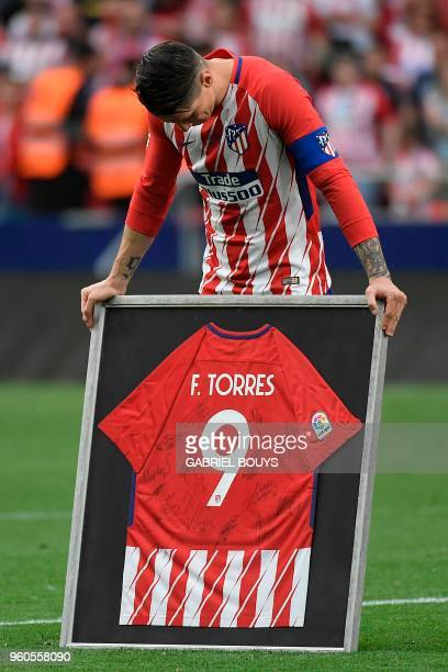 Atletico Madrid's Spanish forward Fernando Torres reacts as he receives a framed jersey signed by teammates during a tribute at the end of the...