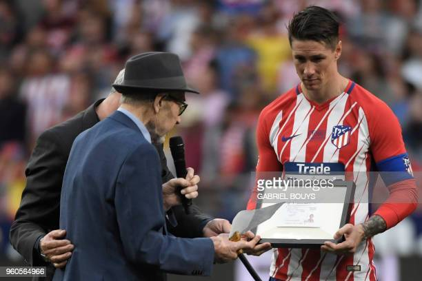 Atletico Madrid's Spanish forward Fernando Torres receives his first club membership from his first coach Manuel Brinas during a tribute at the end...
