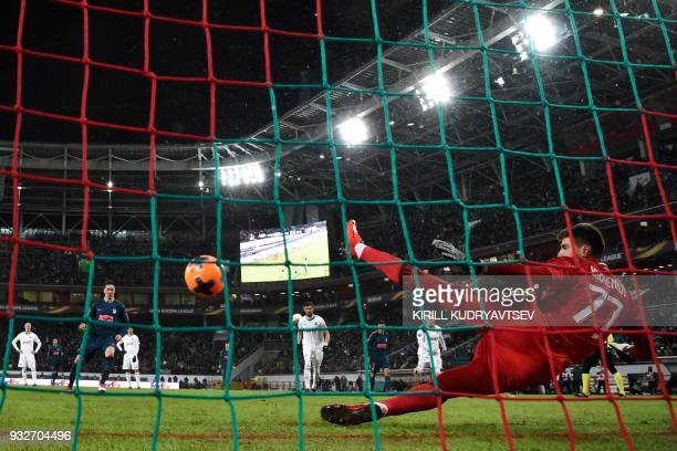 TOPSHOT Atletico Madrid's Spanish forward Fernando Torres scores the team's third goal from a penalty spot past Lokomotiv Moscow's goalkeeper from...
