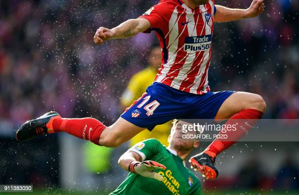 TOPSHOT Atletico Madrid's Spanish midfielder Gabi vies with Las Palmas' Argentinian goalkeeper Leandro Chichizola during the Spanish league football...