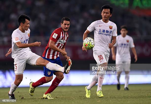 Atletico Madrid's Spanish midfielder Koke and Shanghai's Jiajie Wang and Zhengrong Zhu vie for the ball during a friendly football match between...