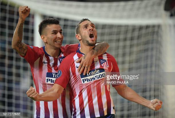 Atletico Madrid's Spanish midfielder Koke celebrates with Atletico Madrid's Argentinian forward Angel Correa after scoring the 24 during the UEFA...