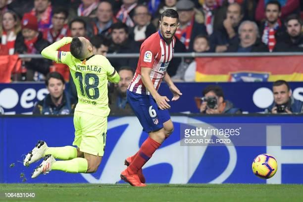 Atletico Madrid's Spanish midfielder Koke challenges Barcelona's Spanish defender Jordi Alba during the Spanish league football match between Club...