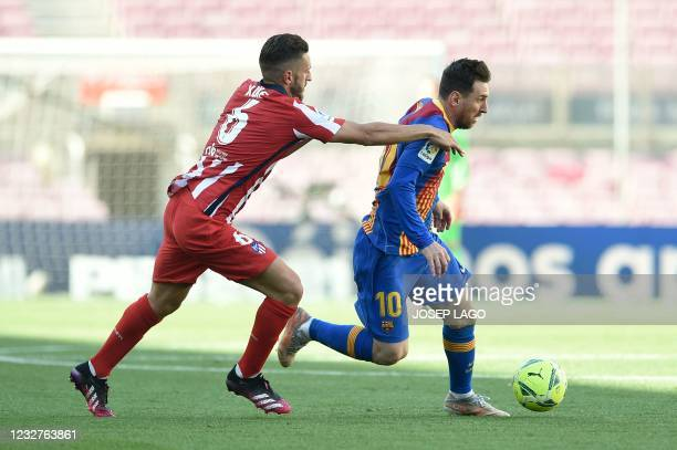 Atletico Madrid's Spanish midfielder Koke challenges Barcelona's Argentinian forward Lionel Messi during the Spanish league football match FC...