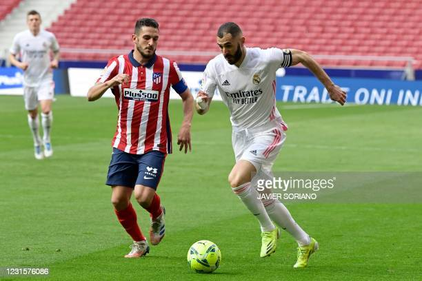 Atletico Madrid's Spanish midfielder Koke challenges Real Madrid's French forward Karim Benzema during the Spanish league football match Club...