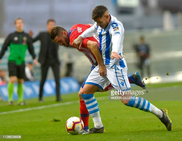 Atletico Madrid's Spanish midfielder Koke challenges Real Sociedad's French defender Theo Hernandez during the Spanish league football match between...