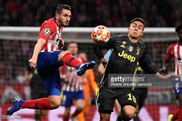 Atletico Madrid's Spanish midfielder Koke vies with Juventus' Argentine forward Paulo Dybala during the UEFA Champions League round of 16 first leg...