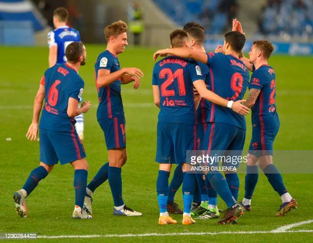 Atletico Madrid's Spanish midfielder Marcos Llorente celebrates with teammates after scoring a goal during the Spanish league football match between...
