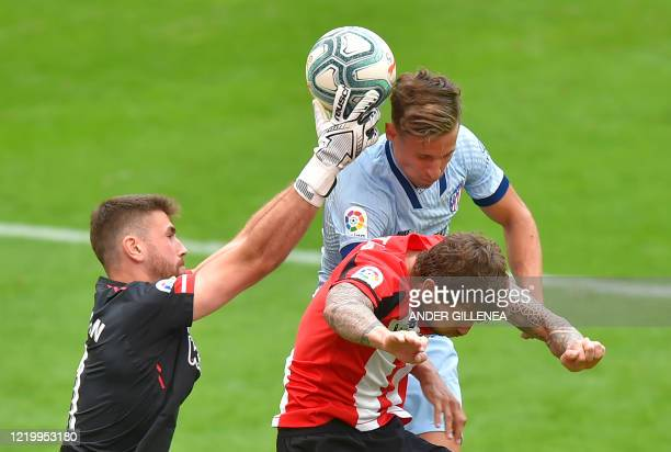 Atletico Madrid's Spanish midfielder Marcos Llorente challenges Athletic Bilbao's Spanish goalkeeper Unai Simon and Athletic Bilbao's Spanish...