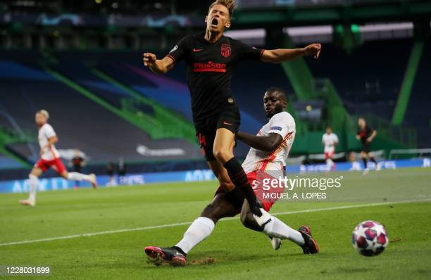 Atletico Madrid's Spanish midfielder Marcos Llorente is tackled by Leipzig's French defender Dayot Upamecano during the UEFA Champions League...