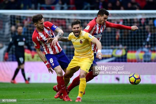 Atletico Madrid's Spanish midfielder Saul Niguez and Atletico Madrid's French defender Lucas Hernandez challenge Girona's Spanish midfielder Cristian...