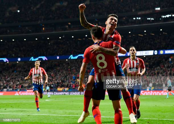 Atletico Madrid's Spanish midfielder Saul Niguez celebrates a goal with Atletico Madrid's Argentinian forward Angel Correa during the UEFA Champions...