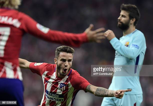 Atletico Madrid's Spanish midfielder Saul Niguez celebrates a goal beside Barcelona's Spanish defender Gerard Pique during the Spanish league...