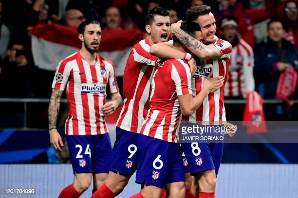 Atletico Madrid's Spanish midfielder Saul Niguez celebrates with teammates after scoring the opening goal during the UEFA Champions League round of...