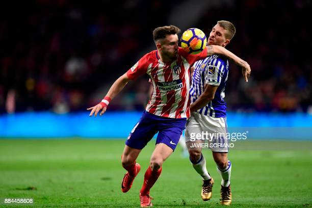 Atletico Madrid's Spanish midfielder Saul Niguez challenges Real Sociedad's Portuguese midfielder Kevin Rodrigues during the Spanish league football...