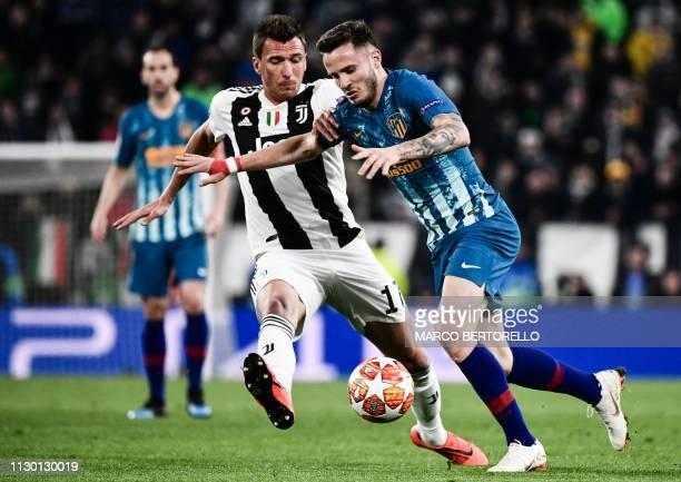 Atletico Madrid's Spanish midfielder Saul Niguez outruns Juventus' Croatian forward Mario Mandzukic during the UEFA Champions League round of 16...
