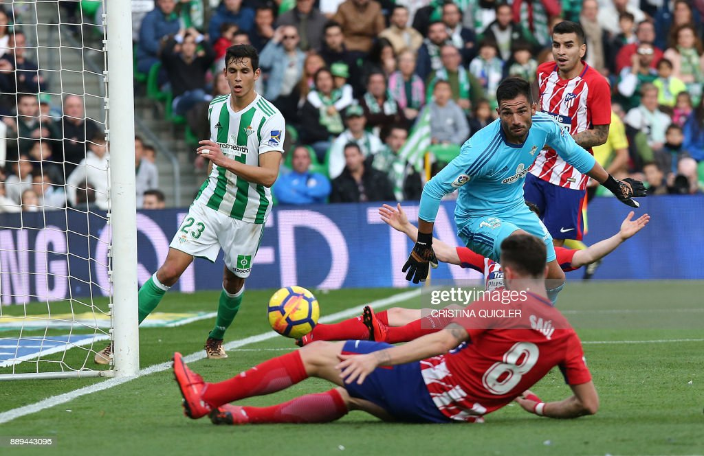 Atletico Madrid's Spanish midfielder Saul Niguez (foreground) scores a goal during the Spanish league football match between Real Betis and Atletico Madrid at the Benito Villamarin Stadium in Sevilla on December 10, 2017. /