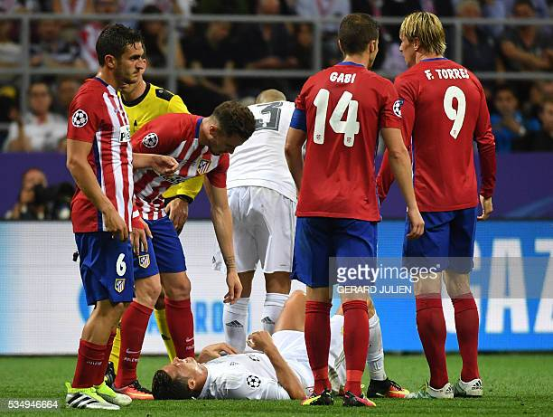 Atletico Madrid's Spanish midfielder Saul Niguez speaks with Real Madrid's Portuguese forward Cristiano Ronaldo lying on the ground surrounded by...