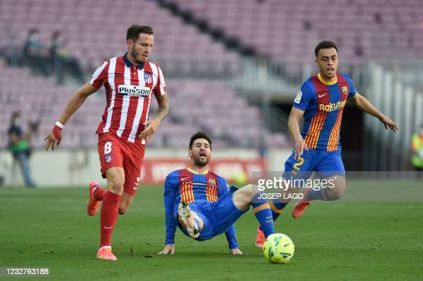 Atletico Madrid's Spanish midfielder Saul Niguez vies for the ball with Barcelona's Argentinian forward Lionel Messi during the Spanish league...